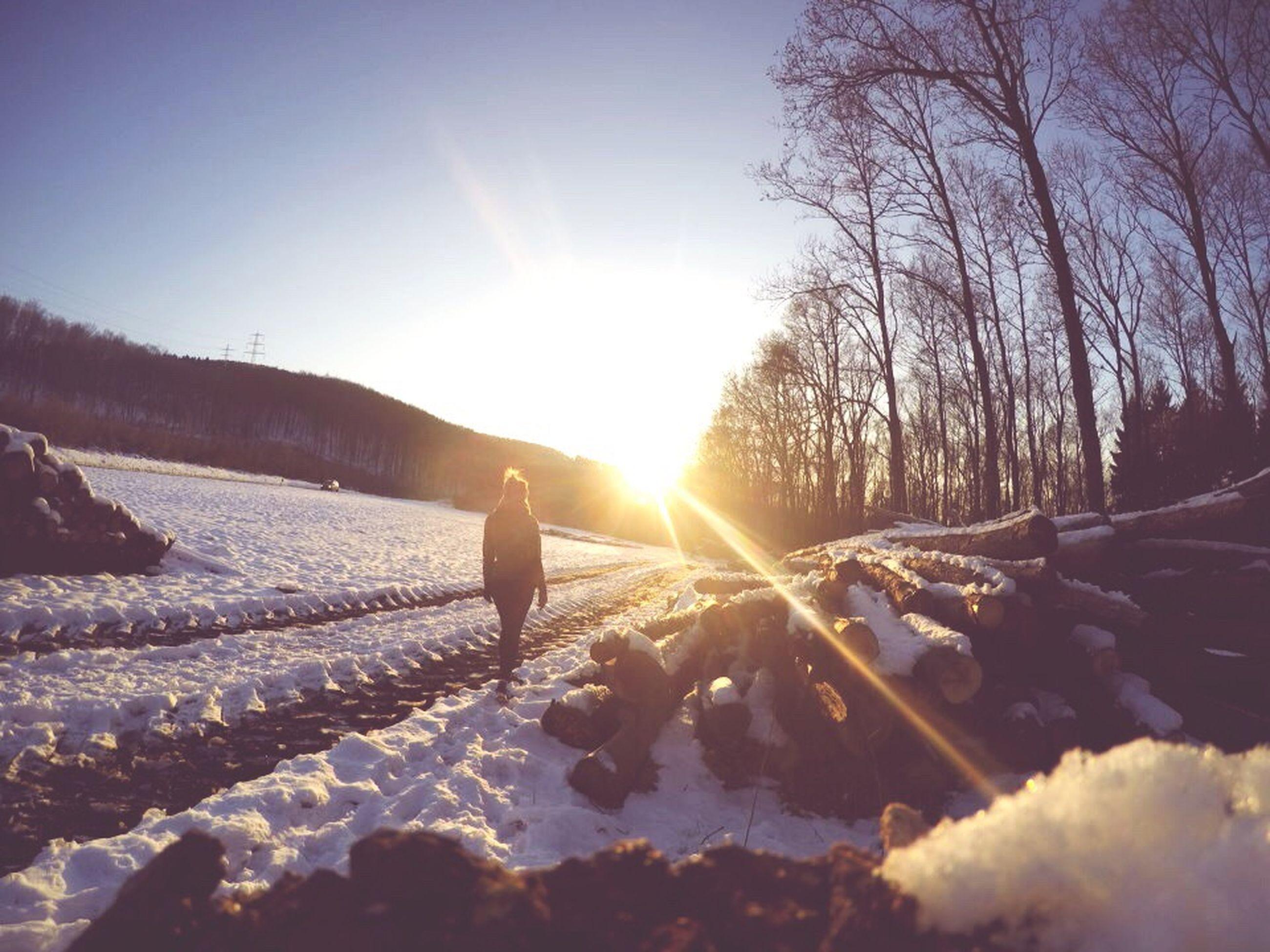 snow, winter, cold temperature, sun, season, sunlight, sunbeam, tranquil scene, tranquility, landscape, silhouette, nature, weather, full length, lens flare, lifestyles, sky, leisure activity