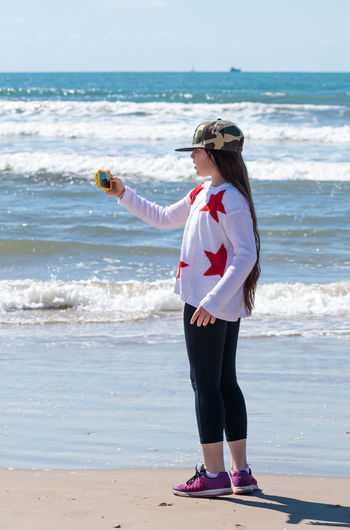 Girl taking selfie through smart phone while standing on sea shore at beach