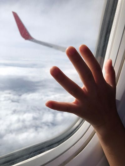 Cropped hand of child touching airplane window