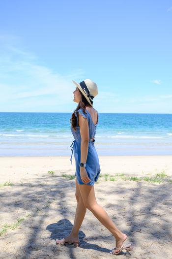 Full length of senior woman on beach against sky