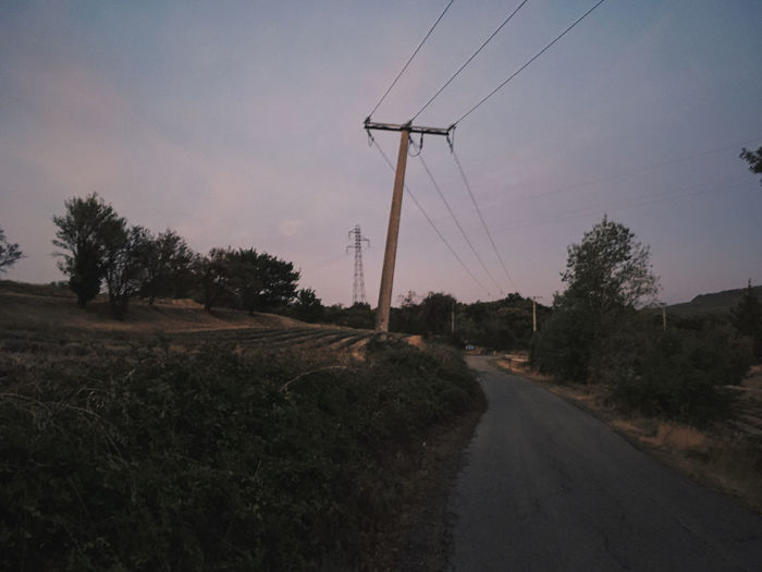 Road by electricity pylon against sky
