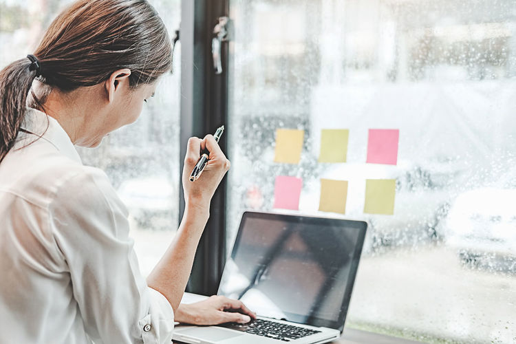 Midsection of woman working with laptop in window
