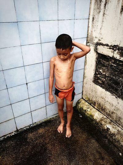 Full length of shirtless boy showering against tiled wall