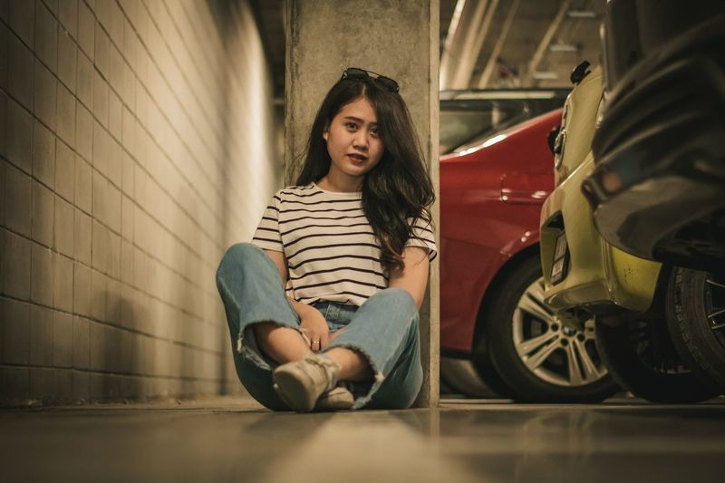 Surface level portrait of woman sitting in parking lot