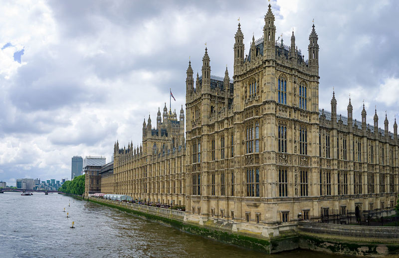 Houses of parliament by thames river against cloudy sky