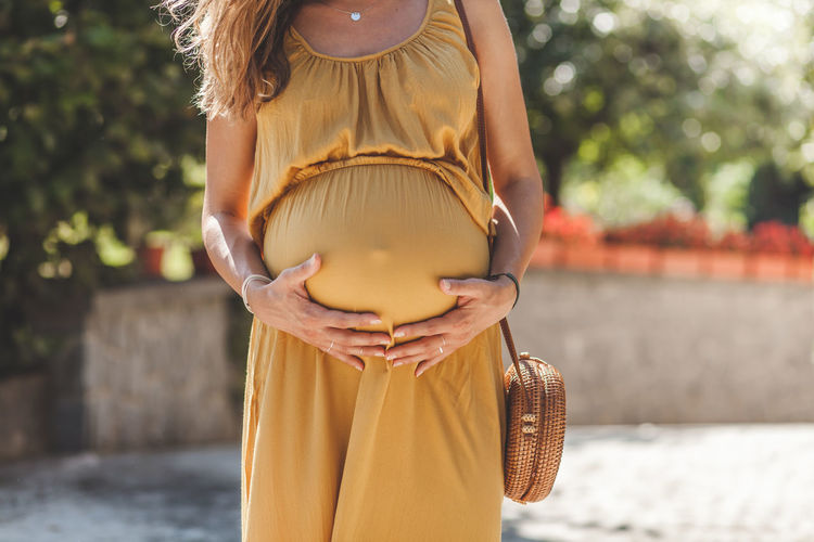 Midsection of pregnant woman holding stomach while standing outdoors