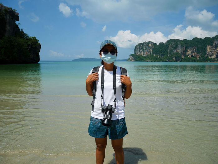 Portrait of woman wearing mask standing at beach