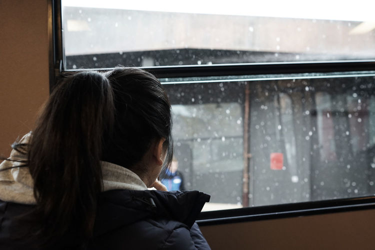 Rear view of woman by wet window
