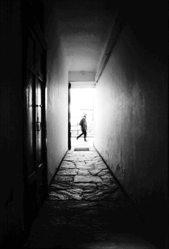 Rear view of silhouette woman walking in corridor of building