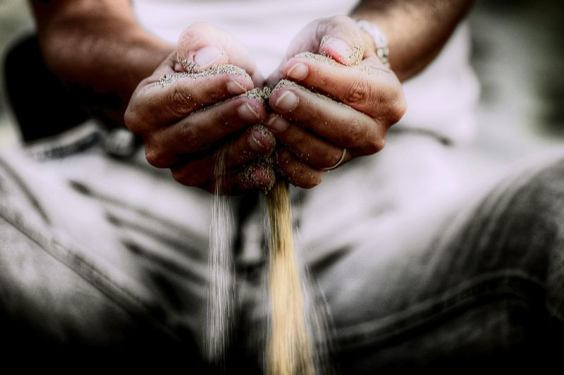 Close-up of hands releasing sand
