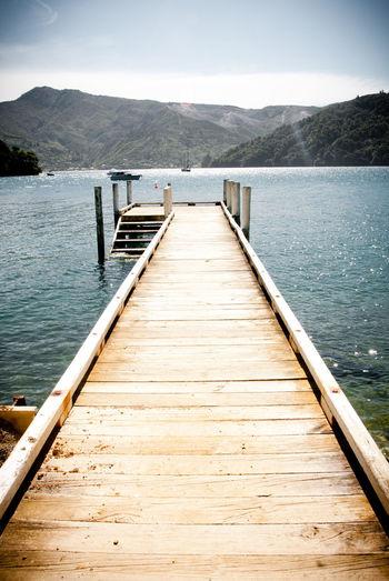 Wooden pier on jetty leading towards lake