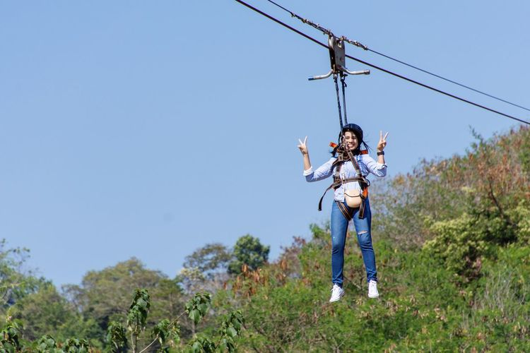 Portrait of woman hanging from safety harness while rappelling against sky