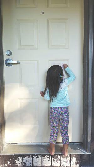 Rear view of girl knocking door