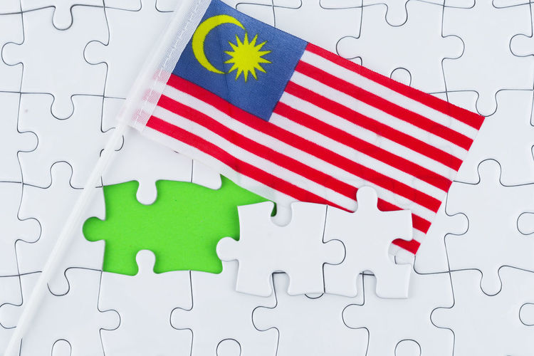 Concept puzzle and Malaysia flag with copy space for word Pattern Puzzle  White Color Shape Flag Jigsaw Piece Indoors  Design Jigsaw Puzzle No People Red Green Color Patriotism High Angle View Solution Connection Multi Colored Full Frame Star Shape Floral Pattern Malaysia Flag