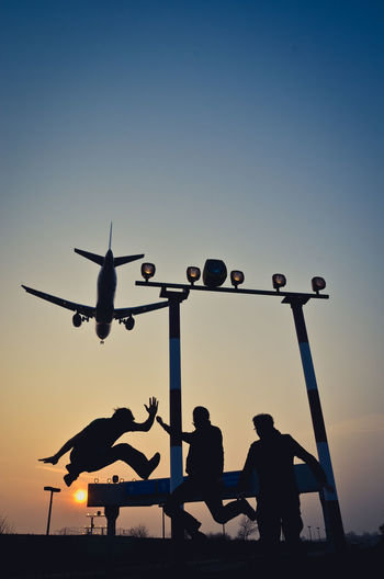 Friends Enjoying With Airplane Flying Against Sky