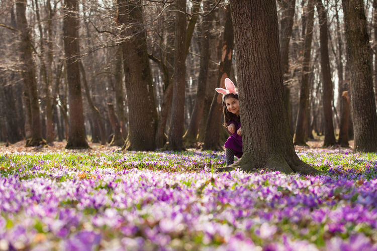 Woman with purple flowers on field by trees in forest