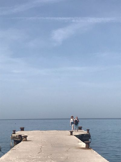 People sitting on promenade by sea against sky