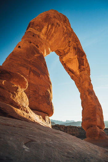 Low angle view of natural arch on rock formation against sky