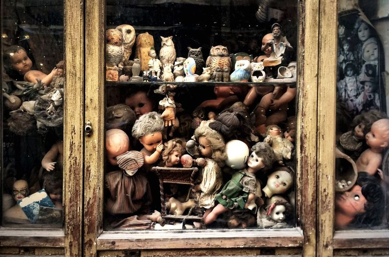 Old Dolls And Toys By Window At Abandoned Store
