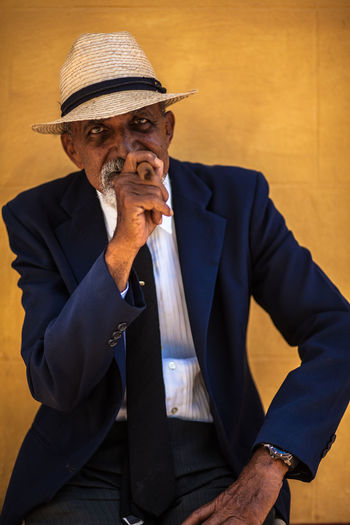 A cuban man poses for tourist' pictures. Casual Clothing Cuba Cuban Leisure Activity Lifestyles Man Old Man People Portrait Portrait Photography Sigar Smoke Smoking Issues Strawhat Strawhatportraits Trinidad Trinidad, Cuba