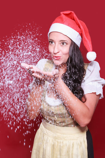 Smiling woman blowing snow against red background