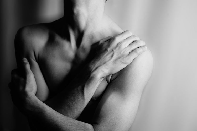 Midsection of man hugging self against wall