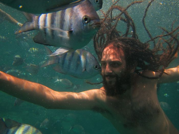 Shirtless man swimming by fishes undersea