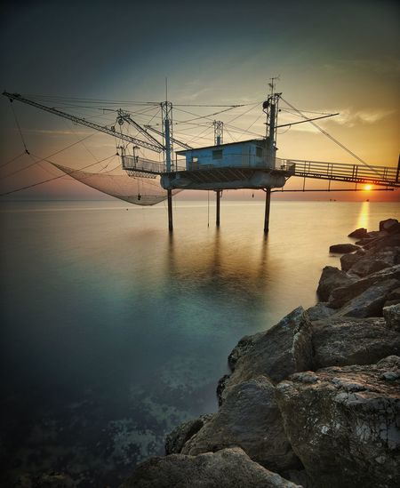 Fishing net in sea against sky during sunset