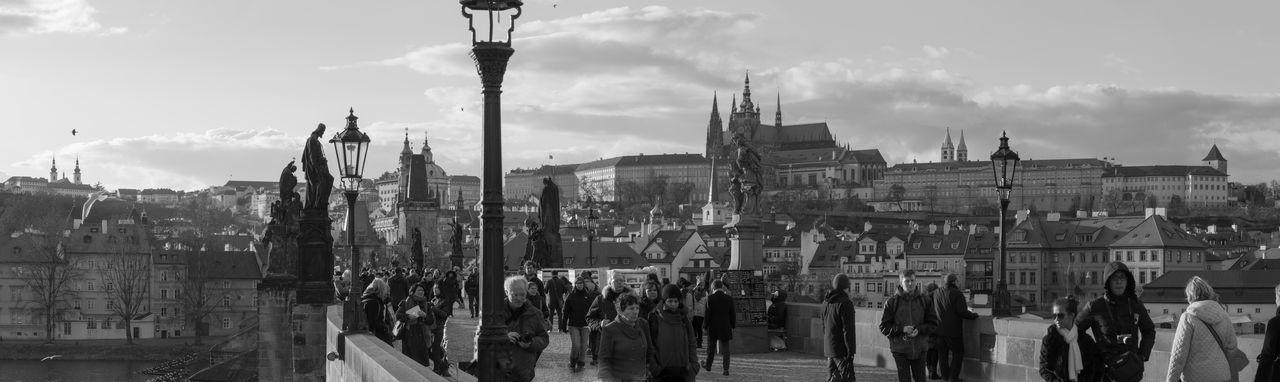 Panoramic view of people walking on charles bridge against sky in city