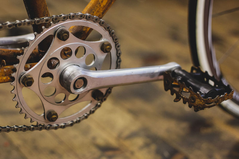 Chain wheel of an old and rusty singlespeed bicycle sitting in a wooden workshop. Aged Antique Bicycle Bicycles Bike Check This Out Circle Closeup Detail Gear Metal Old Orange Color Party Part Of Iron Parts Red Retro Rust Rusty Steel Technology I Can't Live Without Technology Transportation Vintage Wheel