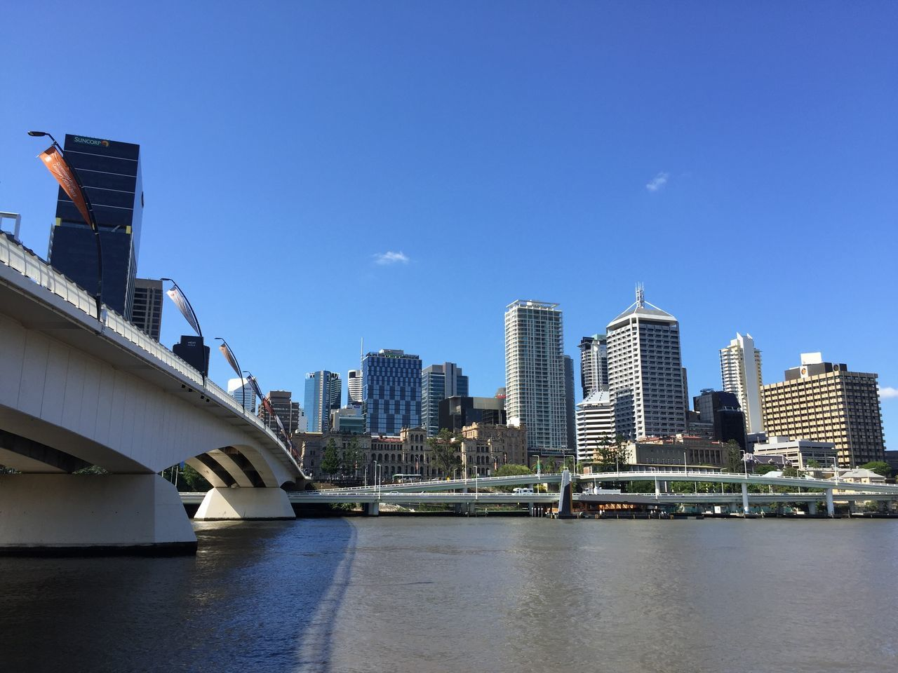 architecture, built structure, building exterior, waterfront, city, skyscraper, modern, bridge - man made structure, river, connection, water, day, outdoors, cityscape, sky, urban skyline, travel destinations, blue, no people, nature