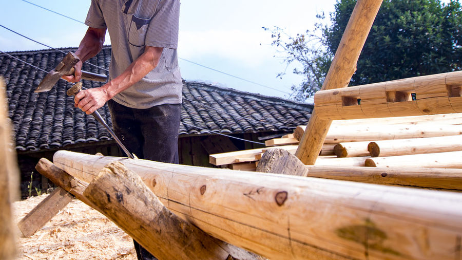 Midsection of male worker carving log at construction site