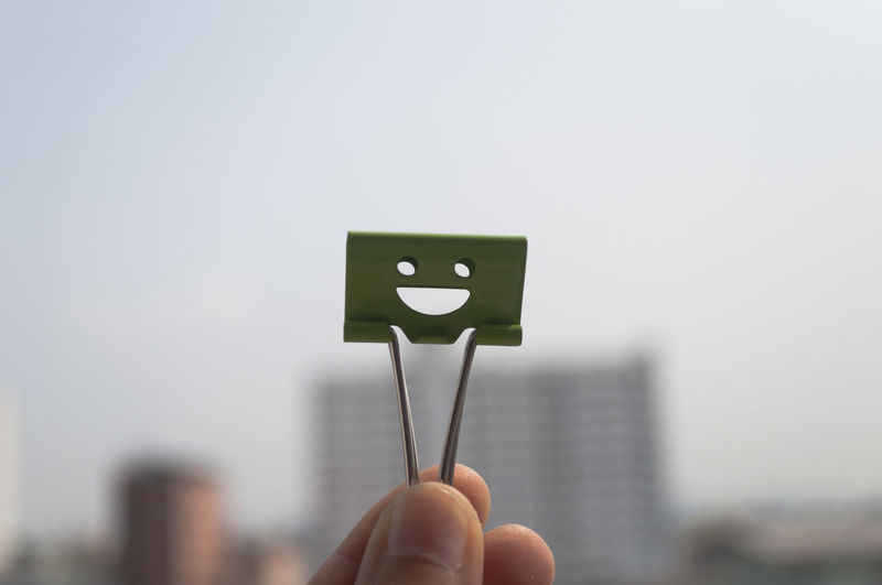 Cropped Hand Holding Smiley Paper Clip Against Clear Sky
