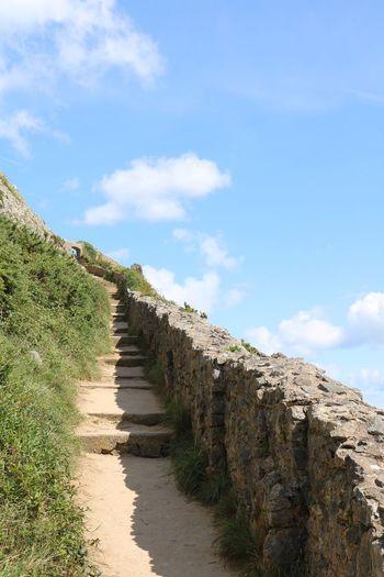 Footpath on mountain against sky
