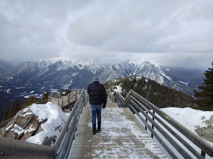 Rear View Of Man Walking On Boardwalk Against Snowcapped Mountains