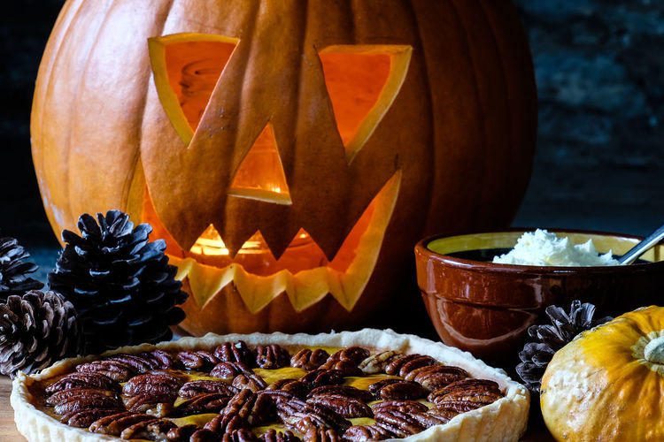 Carved pumpkin and pumkin pie with pecans