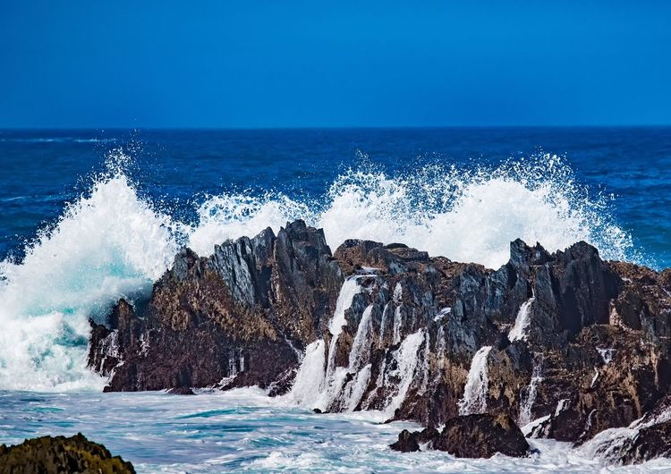 Panoramic view of rocks in sea against blue sky