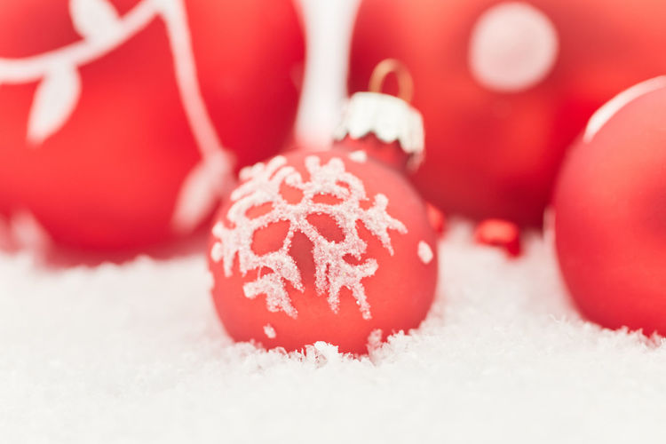 Close-up of red baubles on snow