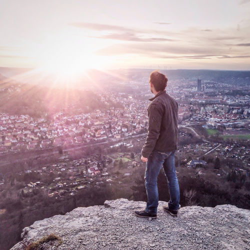 man standing on a Mountain and looks on a city, Jena, Germany Cityscape Leisure Activity Lifestyles Mountain Sun Sunset City Sunlight Outdoors City Life Residential District Casual Clothing Sunbeam Man One Person The Great Outdoors - 2016 EyeEm Awards The Portraitist - 2016 EyeEm Awards