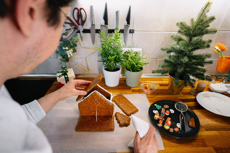 Midsection of man preparing gingerbread house in kitchen at home