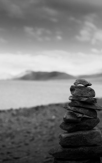 Stack of stones in sea against sky