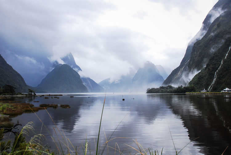 Scenic view of lake by mountains against sky, milford sound