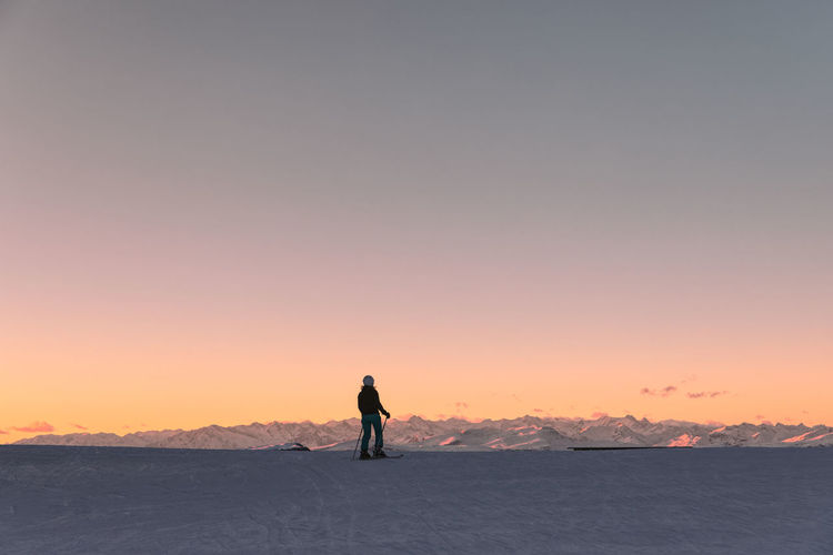 Female skier looking at snowcapped rugged mountains in dolomiti superski resort, italy during sunset