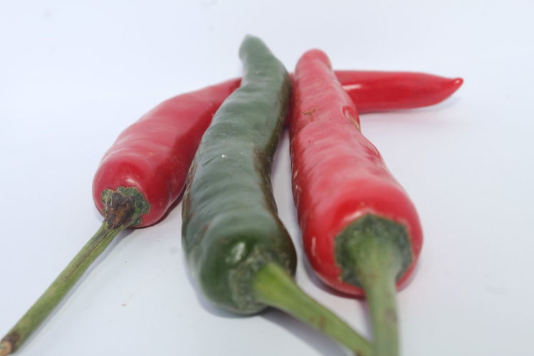 Close-up of chili peppers over white background
