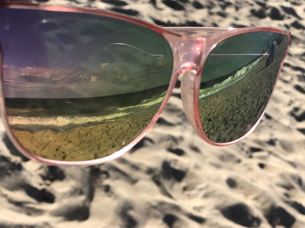 CLOSE-UP OF SUNGLASSES ON GLASS LAND