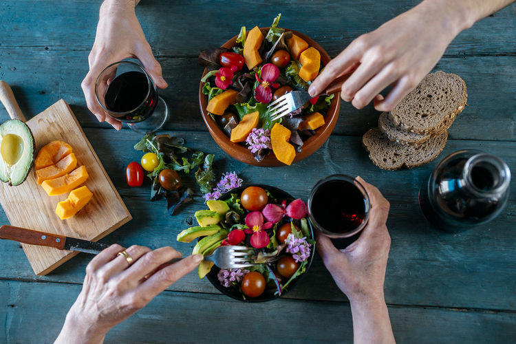 High angle view of hand holding fruits on cutting board