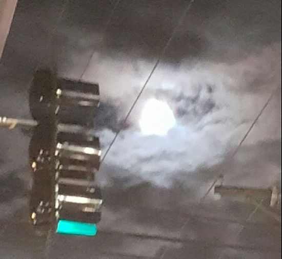 The moon and clouds with green traffic light. Urban Nightsky