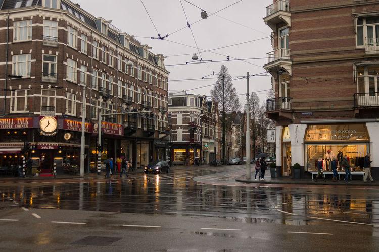 Wet street in city against sky