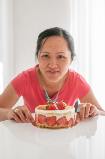 Portrait Of Woman Sitting By Cake On Table At Home