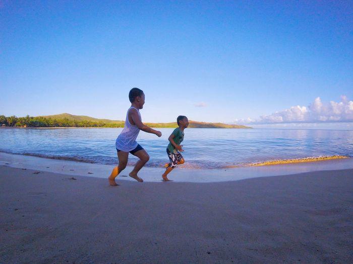 Full length of boys on beach against clear sky